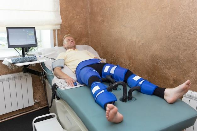 Pressotherapie-maschine auf mann im medizinischen kurzentrum. kosmetische medizinprodukte
