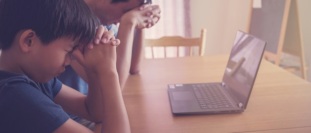 Preteen junge beten mit vater eltern mit laptop, familie und kinder beten online zusammen zu hause