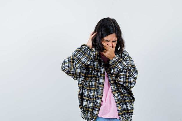 Preteen mädchen, das die hand am mund hält, während es in hemd, jacke gähnt und müde aussieht, vorderansicht.