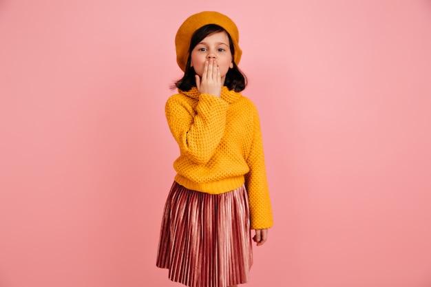 Preteen mädchen im gestrickten pullover, das luftkuss sendet. lustiges kind in gelben kleidern.
