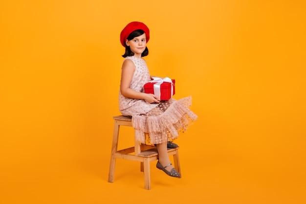 Preteen mädchen im kleid hält geburtstagsgeschenk. kind mit geschenk sitzt auf stuhl auf gelber wand.