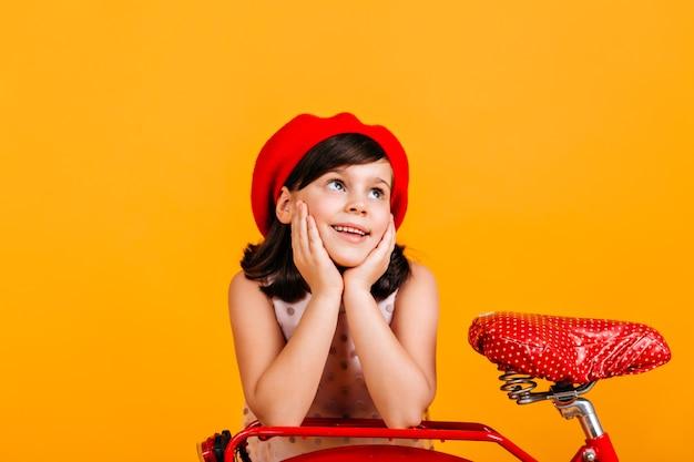 Preteen mädchen in der roten baskenmütze, die mit fahrrad aufwirft. brünettes kind isoliert auf gelb.