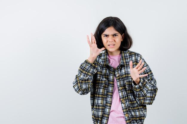 Preteen mädchen in hemd, jacke, die die hände hebt, um sich zu verteidigen und aggressiv zu wirken, vorderansicht. platz für text