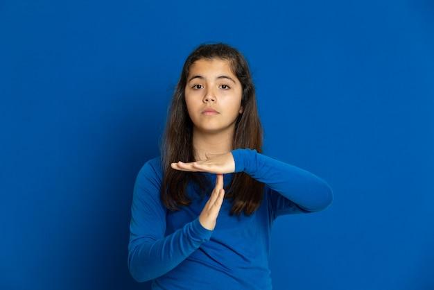 Preteen mädchen mit blauem trikot gestikuliert über blaue wand