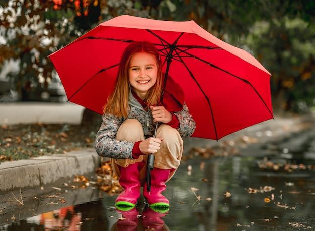 Preteen mädchen mit gummistiefeln sitzen unter regenschirm im herbst auf der straße am regnerischen tag. hübsches weibliches kind in gummistiefeln im freien