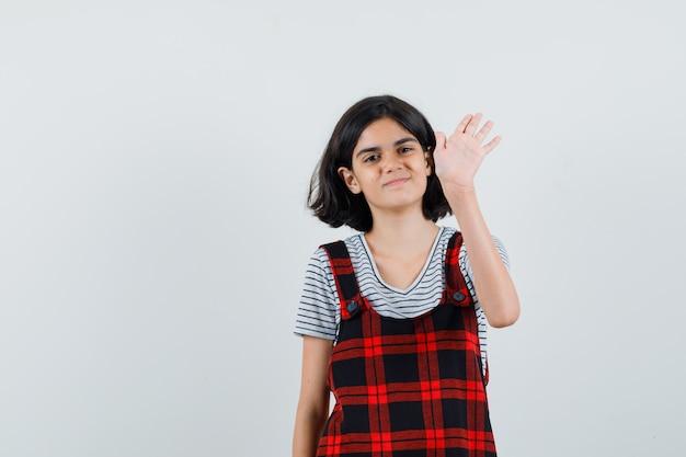 Preteen mädchen winkt hand für gruß in t-shirt, overall, vorderansicht.