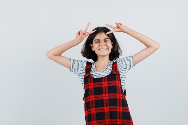 Preteen mädchen zeigt v-zeichen beim lachen in t-shirt, overall und lustig aussehen.