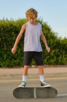 Preteen skater steht auf skateboard in der stadt