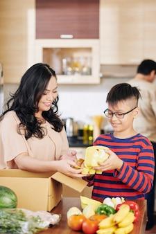 Preteen vietnamesischer junge, der mutter hilft, lebensmittel aus pappkarton zu nehmen