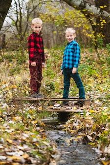 Preteen zwillingsbrüder in karierten hemden stehen in voller länge auf holzteich unter fließendem wasserstrom im herbstwald. fröhliche kindheit und aktives familienwochenende