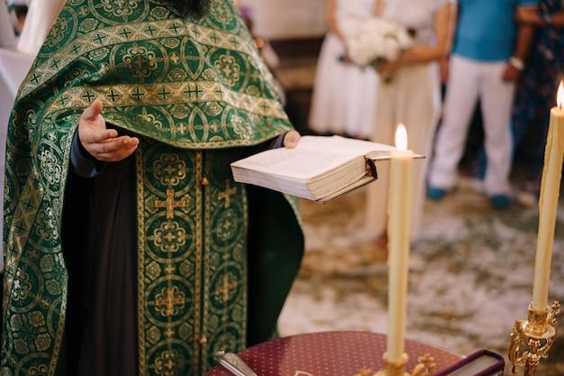 Priester bei der hochzeit hält eine bibel in der hand