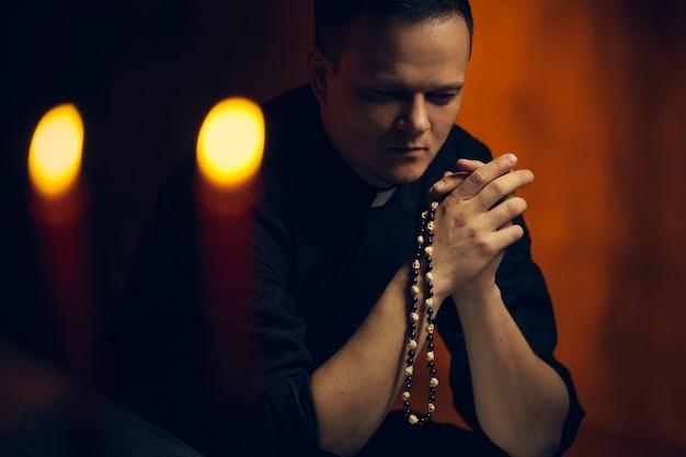 Priester beten. porträt des priesters neben den kerzen betet