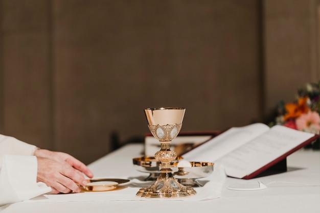 Priester, der den becher während einer hochzeitszeremonie-hochzeitsmesse hält. religion-konzept