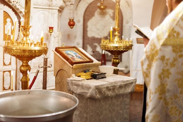 Priester, der goldenes gewand auf zeremonie in christlicher kathedralenkirche, heiliges sakramentales ereignis trägt.