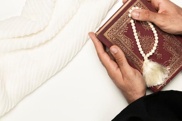 Priester, der heiliges buch und armband hält