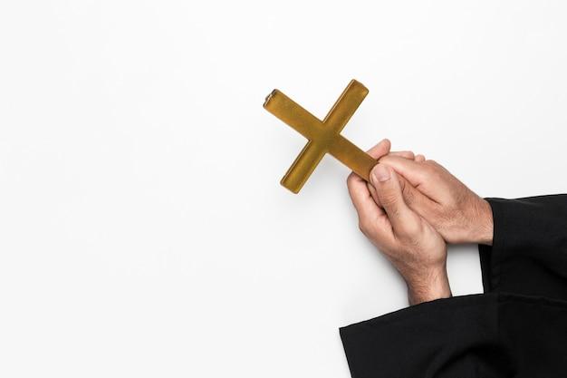 Priester, der heiliges kreuz auf händen hält