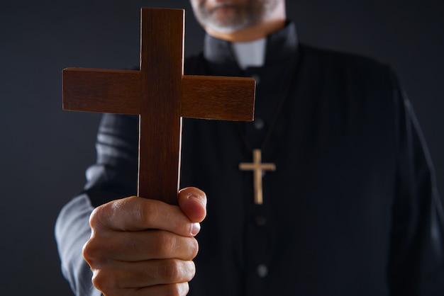 Priester, der kreuz des hölzernen betens hält