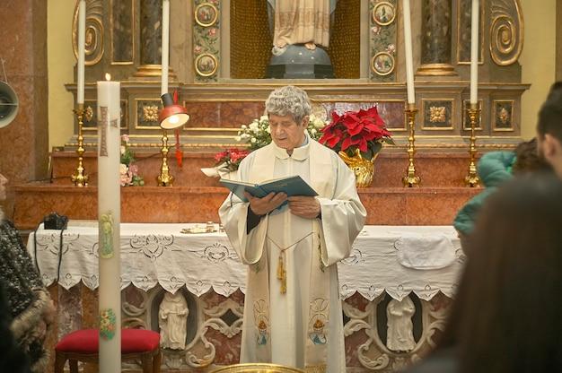 Priester feiert die liturgie in einer katholischen kirche in italien