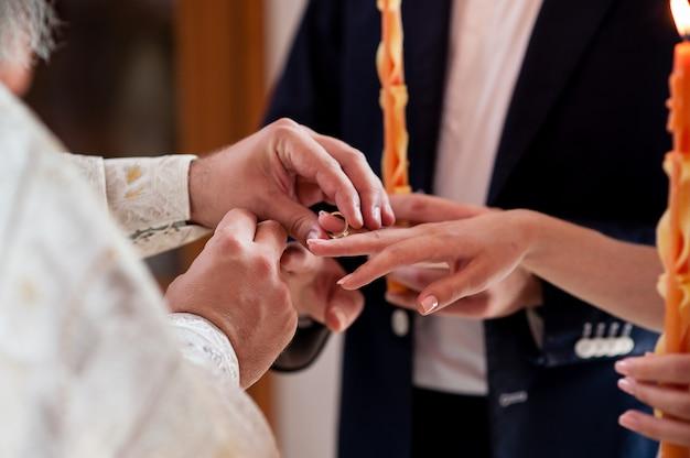 Priester kleidet die ringe für das brautpaar.
