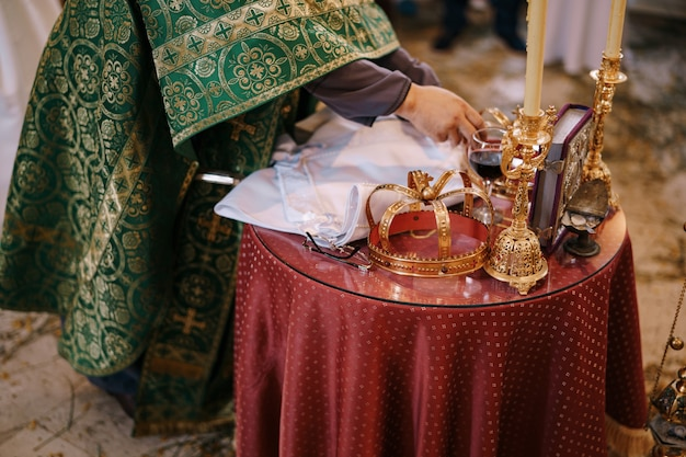 Priester steht vor dem hochzeitstisch mit kronenkerzen und einer bibel