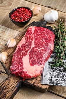 Prime rib eye rohes rindfleisch fleischsteak auf einem metzger holz schneidebrett mit hackmesser auf holztisch. draufsicht.