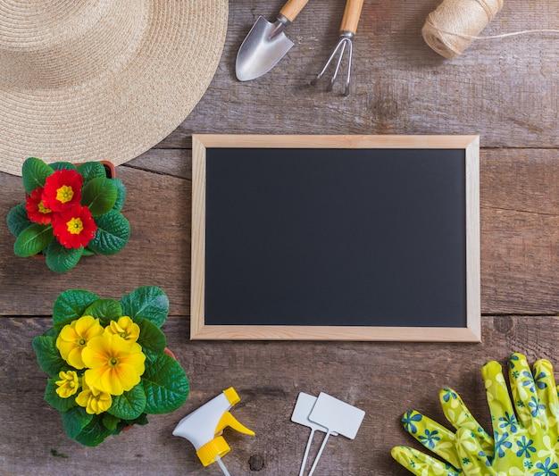 Primel primula vulgaris, gelber und roter garten blüht, eingemacht, werkzeuge, strohhut, gartenarbeitpostkartenkonzept des frühlinges