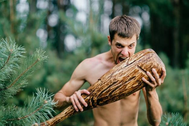 Primitiver nackter mann mit dem riesigen holzstab, der im wald aufwirft