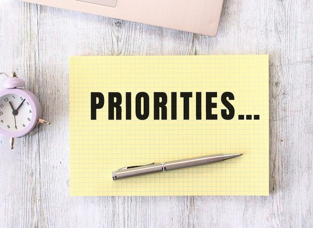 Prioritäten text geschrieben in einem notizbuch, das auf einem hölzernen arbeitstisch neben einem laptop liegt. unternehmenskonzept.