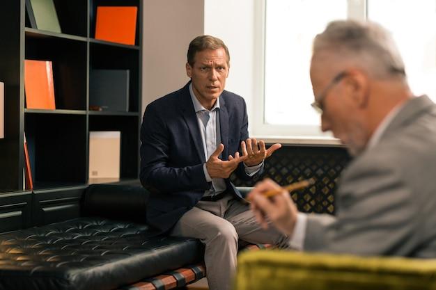 Private unterhaltung. besorgter müder, frustrierter mann, der mit seinem psychotherapeuten spricht, während er ihn ansieht