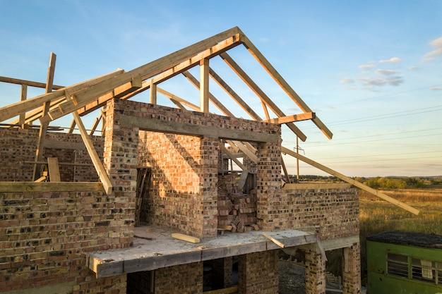 Privates wohnhaus mit holzdachrahmenkonstruktion im bau. unfertiges backsteingebäude in entwicklung.