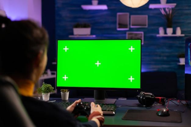Pro gamer, der virtuelle videospiele auf einem professionellen, leistungsstarken computer mit greenscreen-display spielt. cyber-player mit pc mit mock-up-chroma-isolierten desktop-streaming-shooter-spielen mit headset