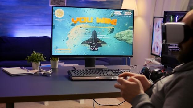Pro gamer gewinnen weltraum-shooter-videospiele mit virtual-reality-kopfhörern und -controllern. konkurrenzfähiger spielermann mit professioneller ausrüstung mit neuer grafik auf einem leistungsstarken computer aus dem spielzimmer