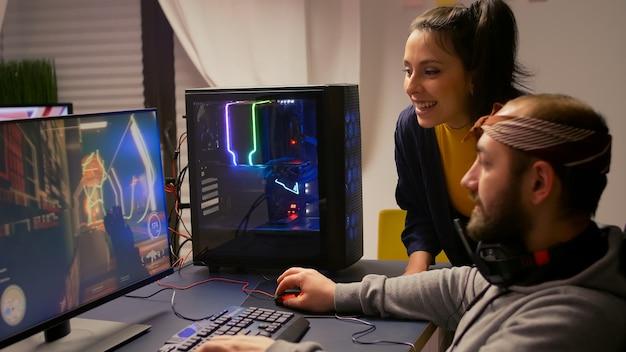Pro gamer-paar, das ein ego-videospiel auf einem leistungsstarken computer mit professionellen kopfhörern spielt. videospieler-streaming-gameplay-cyber-spiel, das auf einem gaming-stuhl mit rgb-ausrüstung sitzt