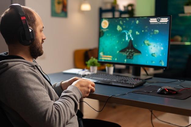 Pro-mann-spieler, der bis spät in die nacht ein videospiel am professionellen computer spielt und kopfhörer trägt. aufgeregter spieler, der einen drahtlosen controller für den virtuellen weltraum-shooter für turnierspiele zu hause verwendet