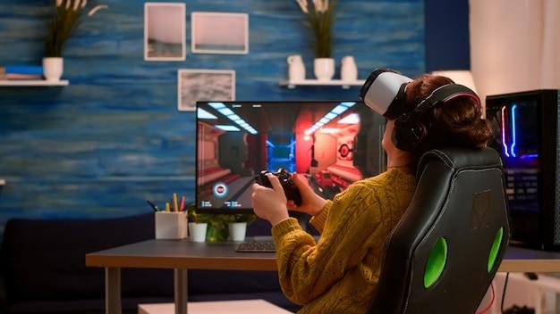 Pro woman e-game cyber, das online mit virtual-reality-headset und wireless-controller spielt