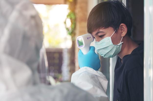 Proaktive häusliche krankenschwester nimmt den temperaturmess-prüfscanner zur hand, um ihn im örtlichen thaiand zu überwachen
