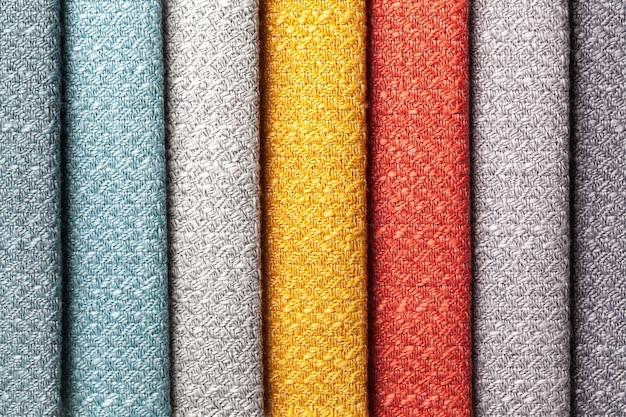 Probe der gewebten textilen roten und grauen farben, hintergrund. katalog und farbton von innenstoff für möbel, nahaufnahme.