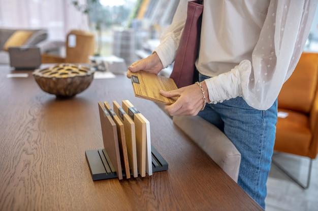Probe von braunem holz für möbel in den händen einer frau, die in der nähe des tisches steht, ihr gesicht ist nicht sichtbar.