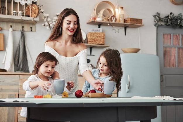 Probieren sie diesen tollen saft. junge schöne frau gibt den kindern getränke, während sie mit spielzeug am tisch sitzen.