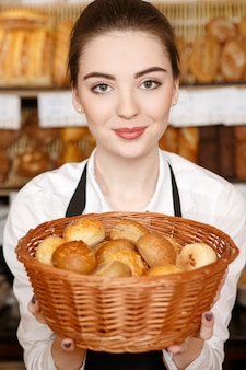 Probieren sie eines davon. vertikale aufnahme einer schönen bäckerin, die einen korb voller frisches brot lächelnd heraushält