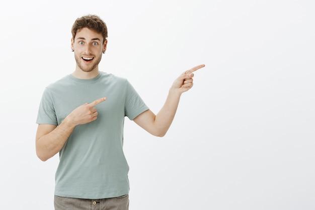 Probieren sie es aus, sehr interessanter ort. positives charmantes männliches model im lässigen t-shirt, das mit den zeigefingern nach rechts zeigt und zufrieden und zufrieden blickt