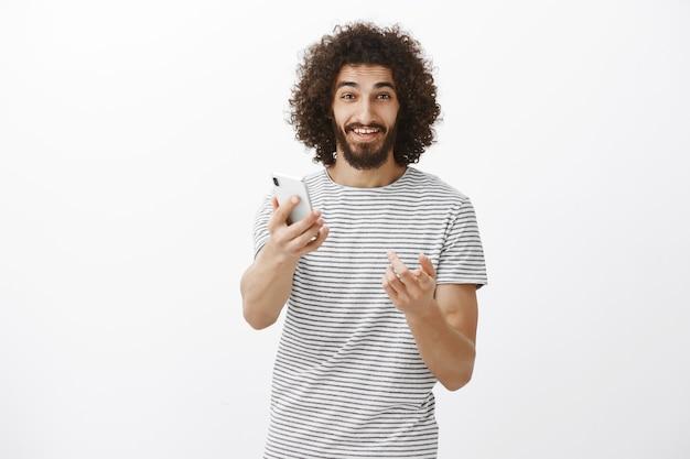 Probieren sie es aus, sie werden ein neues gadget mögen. freundlicher gutaussehender erwachsener mann im gestreiften t-shirt, smartphone in richtung ziehend