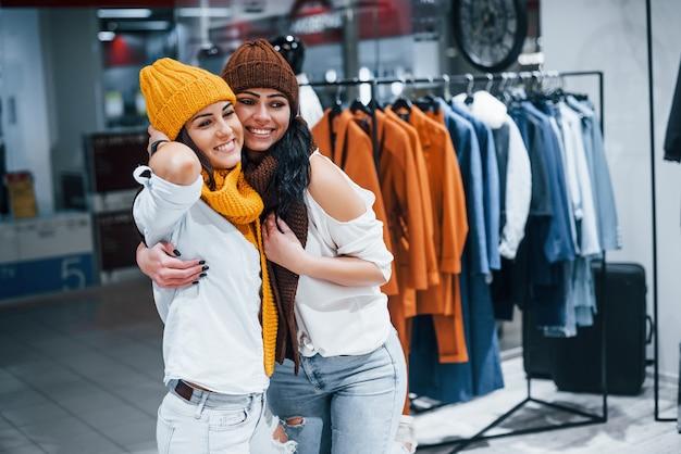 Probieren sie warme mützen und schals aus. zwei junge frauen verbringen gemeinsam einen einkaufstag im supermarkt.