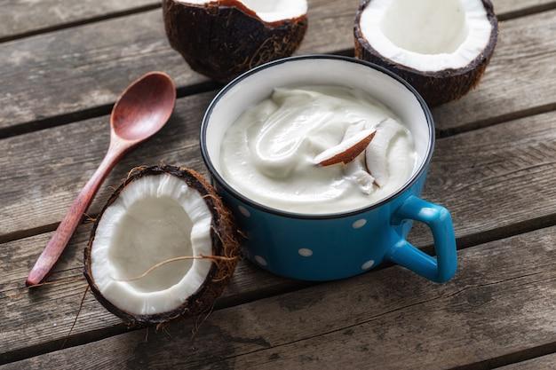 Probiotisches lebensmittelkonzept. bio-kokosjoghurt in der tasse auf rustikalem holztisch