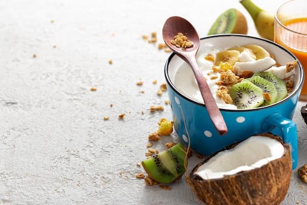 Probiotisches lebensmittelkonzept. schüssel hausgemachten kokos-joghurt mit müsli und frischen früchten auf hellem hintergrund mit kopienraum. gesundes veganes essen. leckeres und gesundes frühstück