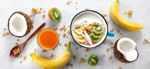 Probiotisches lebensmittelkonzept. schüssel hausgemachten kokosjoghurt mit müsli und frischen früchten auf hellem hintergrund draufsicht. gesundes veganes essen. leckeres und gesundes frühstück