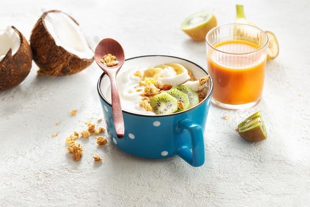 Probiotisches lebensmittelkonzept. schüssel hausgemachten kokosjoghurt mit müsli und frischen früchten auf hellem hintergrund. gesundes veganes essen. leckeres und gesundes frühstück