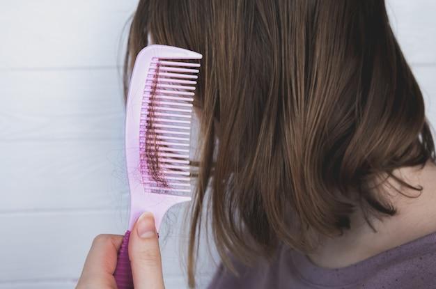 Problem mit haarausfall. frau hält mit rosa kamm.