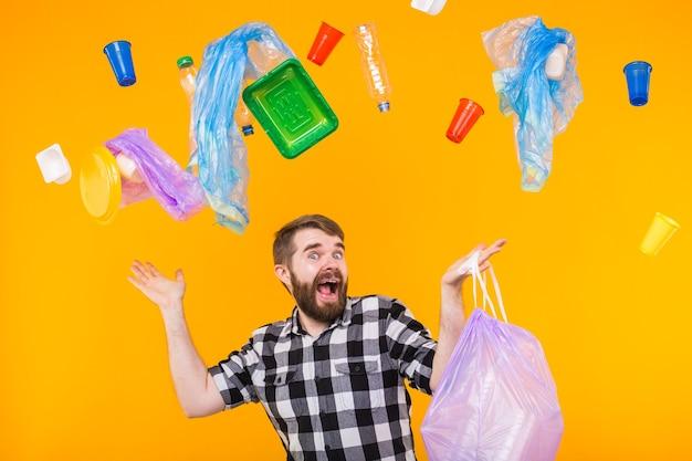 Problem von müll, plastikrecycling, umweltverschmutzung und umweltkonzept - lustiger mann, der müll zum recycling trägt