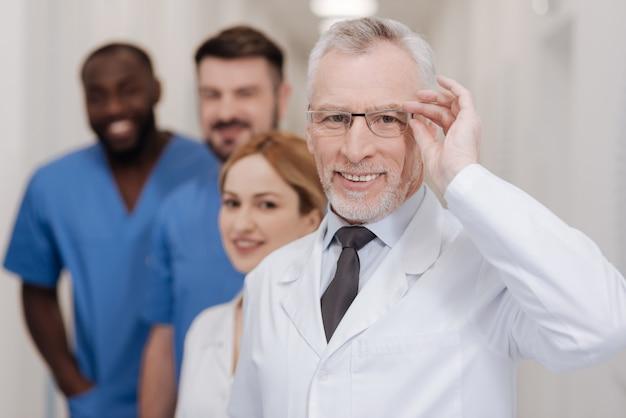 Probleme aufdecken. ein lächelnder, erfahrener arzt, der spaß an der arbeit im krankenhaus hat und die mitarbeiter beim lächeln und berühren der brille präsentiert